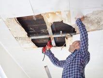 Homme réparant le plafond effondré Photos libres de droits