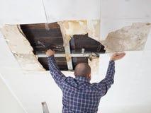 Homme réparant le plafond effondré Images libres de droits