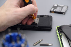 Homme réparant le téléphone portable avec le tournevis Images libres de droits