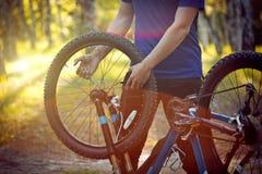 Homme réparant un vélo dans la forêt Photos stock