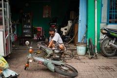 Homme réparant une motocyclette Image stock