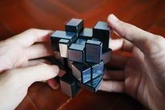Homme résolvant le cube de Rubik formé étrange images stock