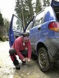 Homme résolvant une crevaison de pneu Images stock