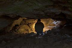 Homme rétro-éclairé explorant la caverne foncée Image libre de droits