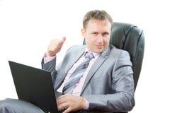 Homme réussi avec l'ordinateur portatif affichant des pouces vers le haut Photographie stock