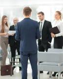 Homme réussi d'affaires se tenant avec son personnel à l'arrière-plan à Photographie stock libre de droits