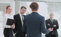 Homme réussi d'affaires se tenant avec son personnel à l'arrière-plan à Image libre de droits
