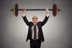 Homme réussi d'affaires soulevant sans effort le barbell lourd Image libre de droits