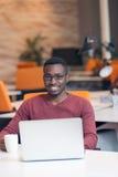 Homme réussi de sourire bel d'Afro-américain à l'aide de l'ordinateur portable Photographie stock libre de droits