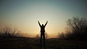 Homme réussi heureux célébrant pendant le lever de soleil ou le coucher du soleil Heureux et gratuit Le type soulève ses mains et clips vidéos