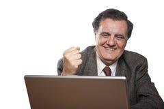 Homme réussi heureux d'affaires avec un ordinateur portatif Photographie stock