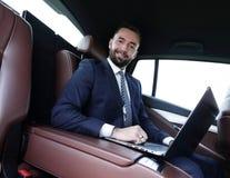 Homme réussi travaillant avec l'ordinateur portable se reposant dans la voiture Image stock
