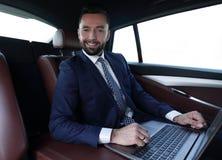 Homme réussi travaillant avec l'ordinateur portable se reposant dans la voiture Photo libre de droits