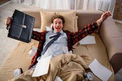 Homme radieux exultant sur le sofa à la maison images stock