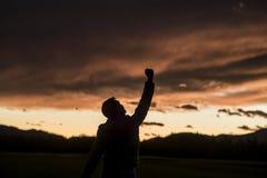 Homme radieux soulevant son poing contre un coucher du soleil photos libres de droits