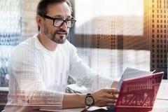 Homme raidi agréable dans des lunettes lisant des rapports photo stock