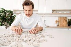 Homme raidi faisant un puzzle denteux Image stock
