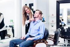 Homme rasé par la femme de coiffeur Photographie stock