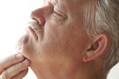Homme rayant sous son menton Photo stock
