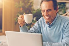 Homme rayonnant buvant de son café et à l'aide de l'ordinateur portable à la maison Image stock