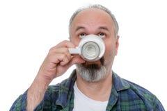 Homme recherchant tout en buvant du café de matin Images libres de droits