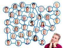Homme regardant au groupe social de réseau Photo libre de droits
