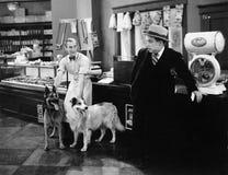 Homme regardant craintif deux chiens dans un magasin de boucher (toutes les personnes représentées ne sont pas plus long vivantes Photo libre de droits