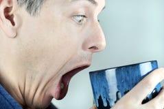 Homme regardant dans la tasse dans la stupéfaction Images stock