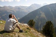 Homme regardant des Mountain View avec binoche Images stock