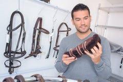 Homme regardant des protège-tibia dans la boutique équestre image stock