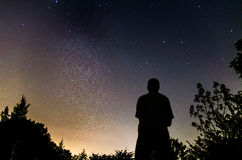 Homme regardant fixement le ciel nocturne avec la manière laiteuse Image stock