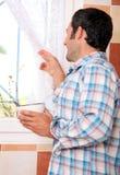 Homme regardant hors de la fenêtre Photo stock