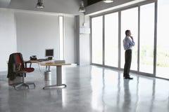 Homme regardant hors de la porte en verre dans le bureau vide Images stock