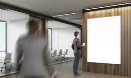 Homme regardant l'affiche dans le bureau Image libre de droits