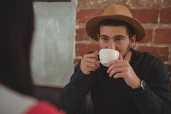 Homme regardant l'amie tout en buvant du café Photos stock