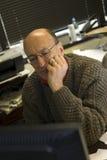 Homme regardant l'écran d'ordinateur dans le bureau Image libre de droits