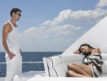 Homme regardant la femme dormant sur Sofa In Yacht photographie stock