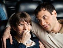 Homme regardant la femme pleurant tout en observant le film Image stock