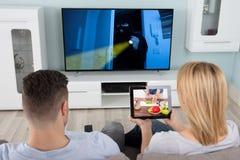 Homme regardant la télévision avec son épouse à l'aide de la Tablette Images libres de droits