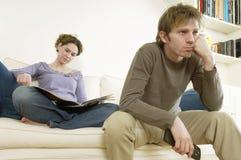 Homme regardant la TV avec la magazine de lecture de femme Image libre de droits