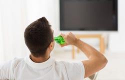 Homme regardant la TV et buvant de la bière à la maison Image stock