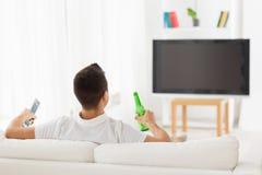 Homme regardant la TV et buvant de la bière à la maison Photographie stock libre de droits