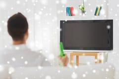 Homme regardant la TV et buvant de la bière à la maison Images libres de droits