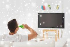 Homme regardant la TV et buvant de la bière à la maison Photographie stock