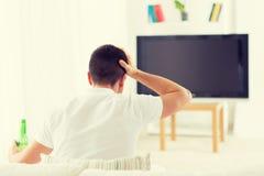 Homme regardant la TV et buvant de la bière à la maison Photos libres de droits