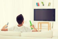 Homme regardant la TV et buvant de la bière à la maison Images stock