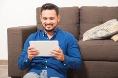 Homme regardant la TV sur une tablette image stock