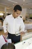 Homme regardant la vaisselle de cuisine dans le magasin de meubles image stock