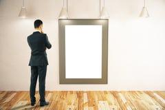 Homme regardant le cadre de tableau Photo stock