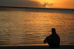 Homme regardant le coucher du soleil au-dessus des Îles Maurice photographie stock libre de droits